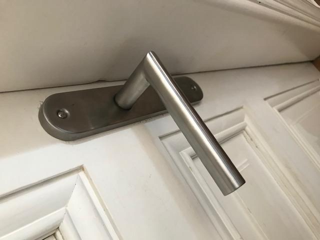Nettoyage d'une poignée de porte avec une lingette désinfectante